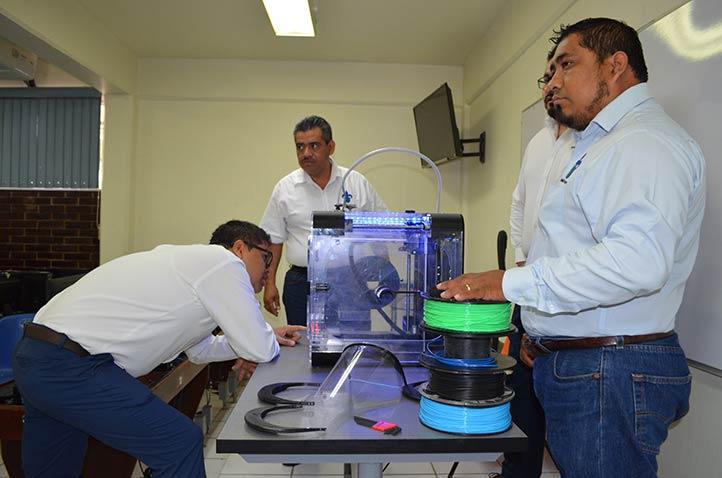 Ajustando la impresora con el material por parte de los académicos