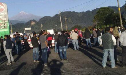 Taxistas bloquean la carretera Huatusco-Xalapa exigiendo la renuncia del titular de Transporte Público.